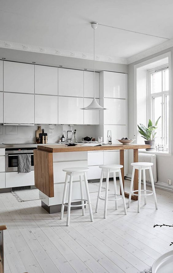 a glossy white minimalist kitchen with a grey countertop, a small kitchen island in white and stained wood, white stools