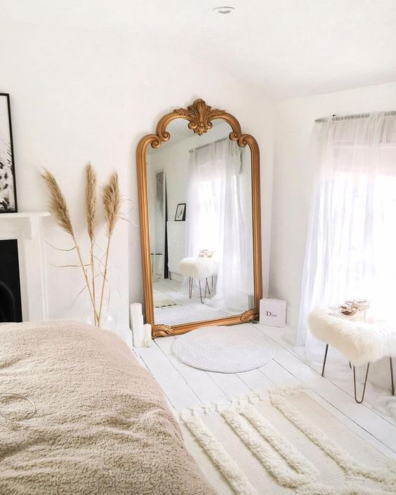 a lovely Scandinavian bedroom with an oversized mirror in a gilded frame, a bed, a fireplace and some Moroccan-style rugs