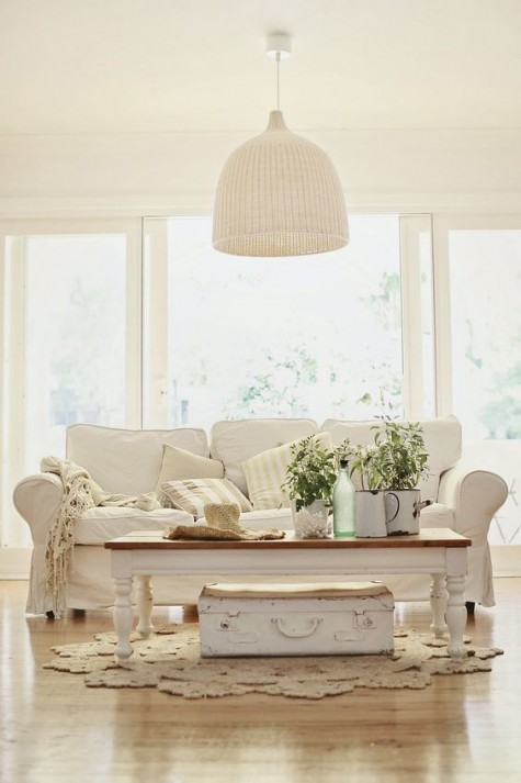 a shabby chic beach cottage living room with a white Ektorp sofa, a low coffee table, a suitcase, a white rattan pendant lamp
