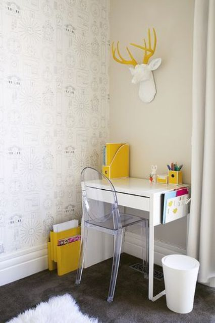 a small and sleek white desk with a drawer, a ghost chair, yellow organizers and a faux taxidermy piece for a lovely working or studying nook