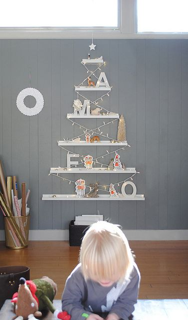 a wall-mounted Christmas tree done with IKEA Ribba ledges, lights, letters and figurines is a pretyt alternative to a usual tree