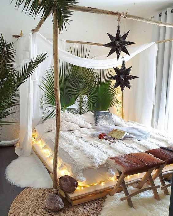 a boho bedroom with a canopy bed styled with lights, hanging star lanterns and curtains, large palm leaves and wooden stools