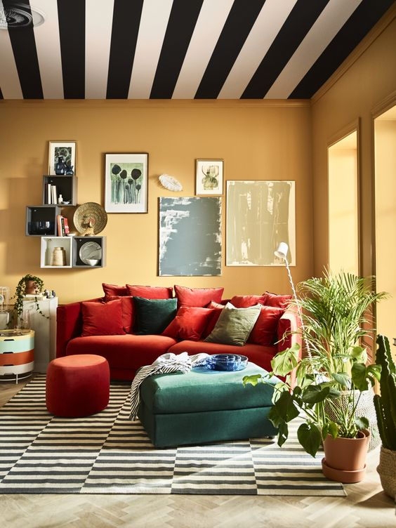 a colorful living room with yellow walls, a fiery red Stockholm, a green ottoman and a pretty gallery wall plus a striped ceiling