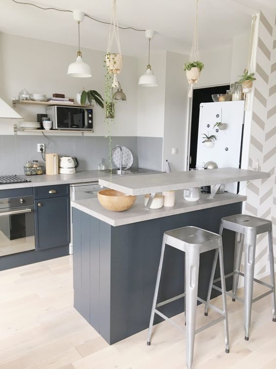 a graphite grey kitchen with a grey tile backsplash, a matching grey kitchen island with a raised countertop