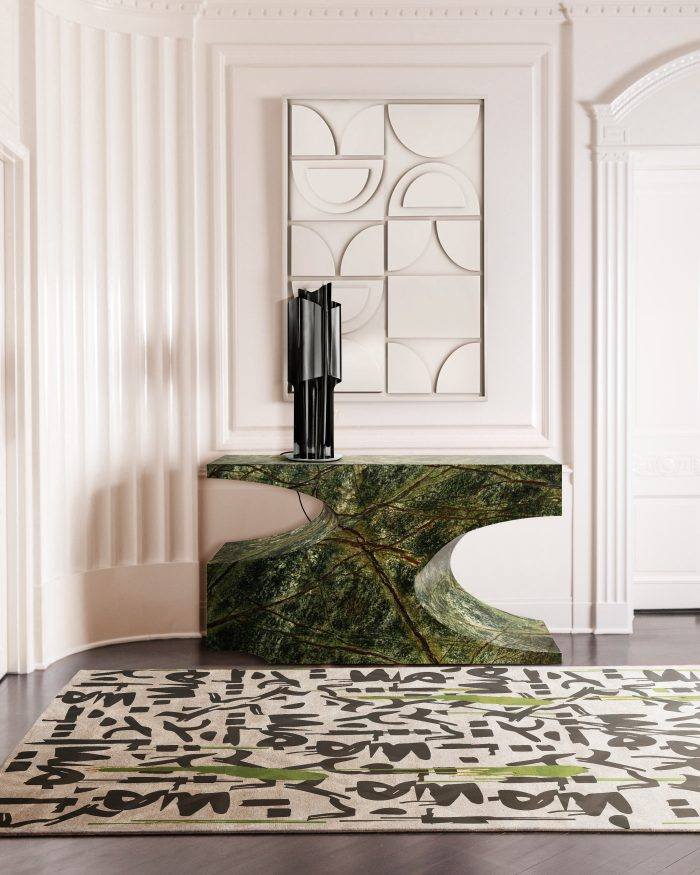 a refined entryway with a gorgeous stone carved console, a graphic rug with green touches and a table lamp