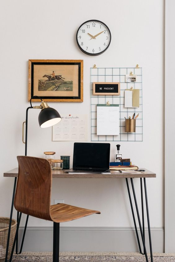 17 a small home office with a sleek desk with hairpin legs, a grid with mems and some art, a plywood chair and a table lamp
