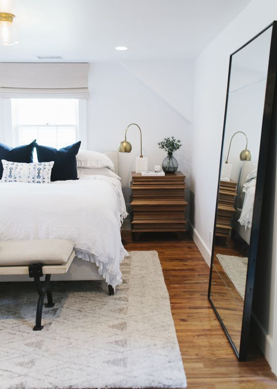 a stylish modern bedroom with neutral furniture, a wooden nightstand, an oversized mirror in a black sleek frame and gilded touches