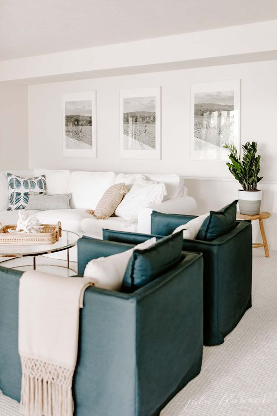 a stylish tropical living room with a white Ektorp sofa, teal leather chairs, a glass round table and a chic gallery wall