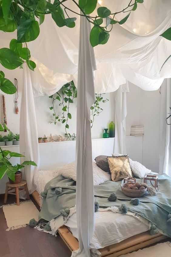 a boho bedroom with a pallet canopy bed styled with curtains, lights and greenery, potted plants and cool bedding