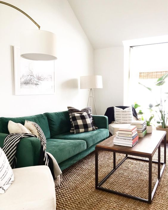 18 a cozy living room with a hunter green Stockholm sofa, a wooden table and creamy chairs and stacks of books