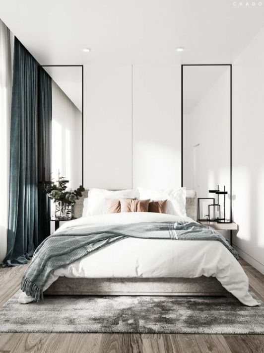 a serene contemporary bedroom with tall and narrow mirrors on both sides, a comfy bed and teal curtains for a touch of color