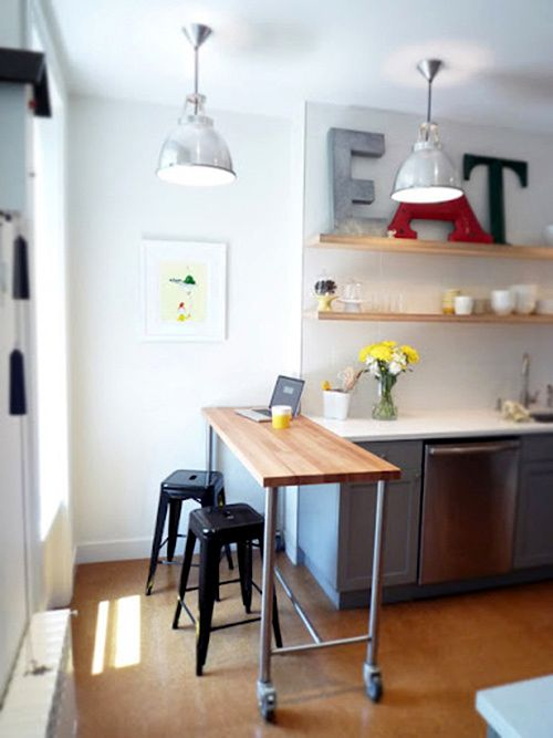 a small breakfast bar formed with a large metal and wood cart, black stools - you can move the cart anytime