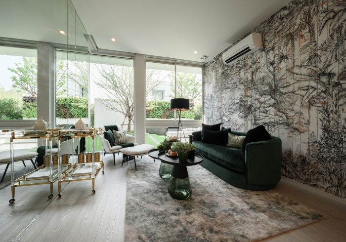 a stylish living room with a map accent wall, a dark green sofa, green tables and pillows and a bar cart plus a glazed wall
