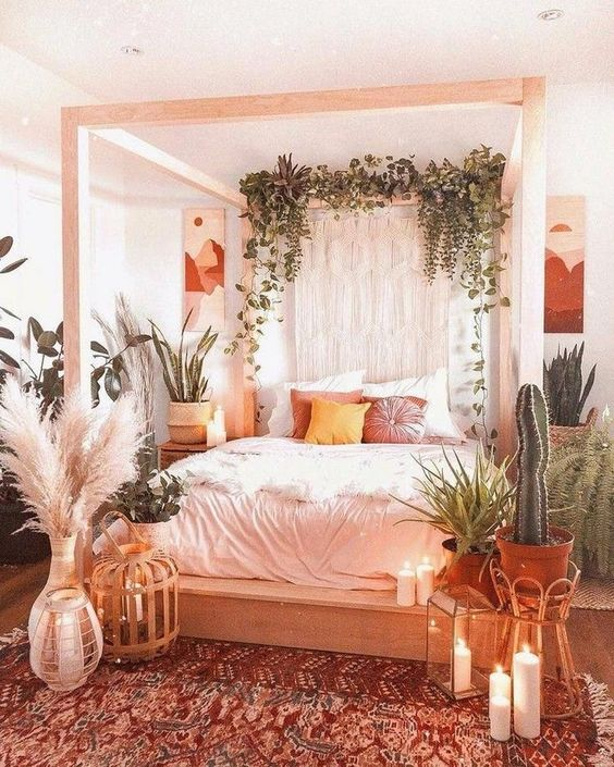a boho bedroom with a wooden canopy bed, greenery and macrame, potted cacti and plants, candles and neutral bedding