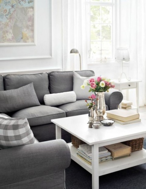 a cozy farmhouse living room with a grey L-shaped Ektorp sofa, a low white table, cool vintage lamps and a pastel artwork on the wall