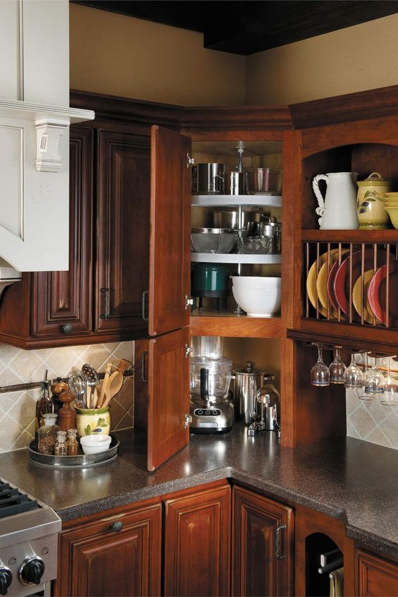 a dark stained kitchen with a diagonal cabinet and swivel trays inside is a cool idea to hide everything you don't need