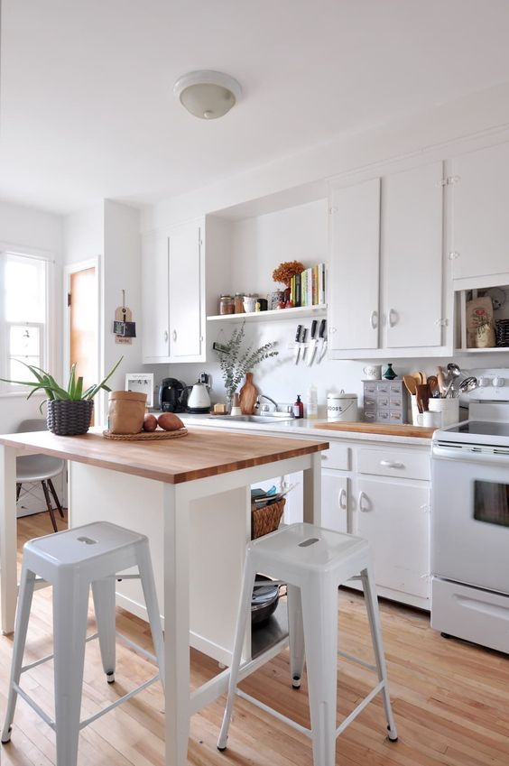a lovely crispy white kitchen with butcherblock countertops, a small kitchen island that doubles as an eating space