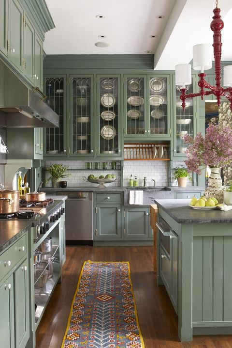a lovely vintage inspired green kitchen with grey stone countertops and a white subway tile backsplash plus a red chandelier