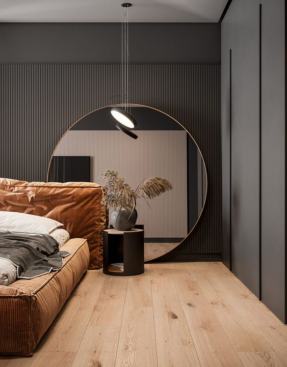 a refined and moody bedroom with a black wooden slab wall, a round mirror, an upholstered bed and pendant lamps