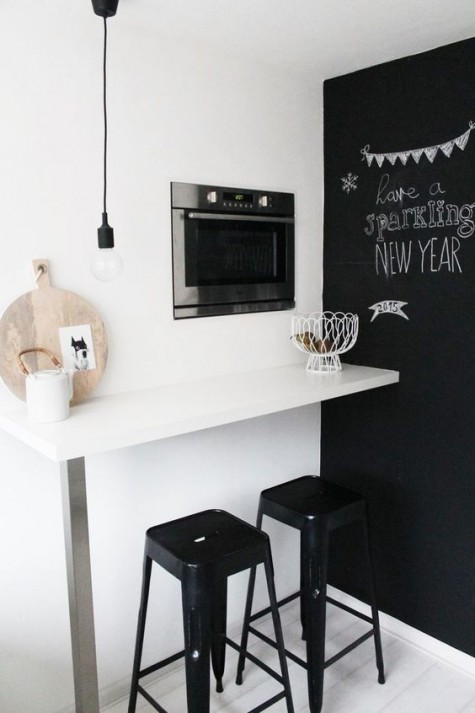 a small minimalist breakfast bar with a wall mounted countertop, a built in oven for warming up sandwiches and black stools