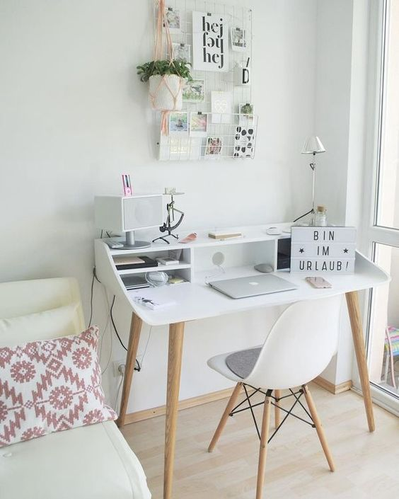 a small modern desk with open storage compartments, a grid on the wall and a matching white chair