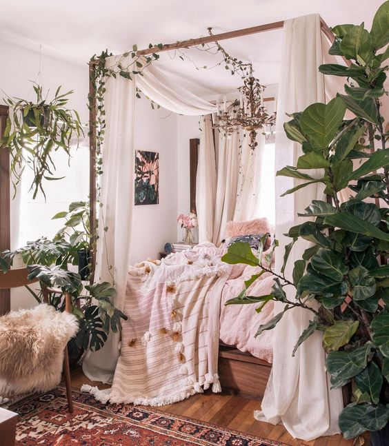a boho jungle bedroom with mid-century modern furniture, neutral curtains, pastel and neutral bedidng and lots of greenery and statement plants
