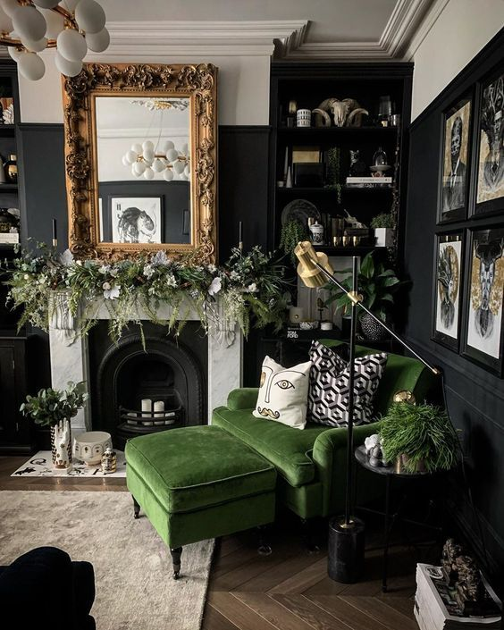20 a moody living room with black walls, a non-working fireplace, a mirror in a vintage frame, a grene chair and a footrest, potted plants