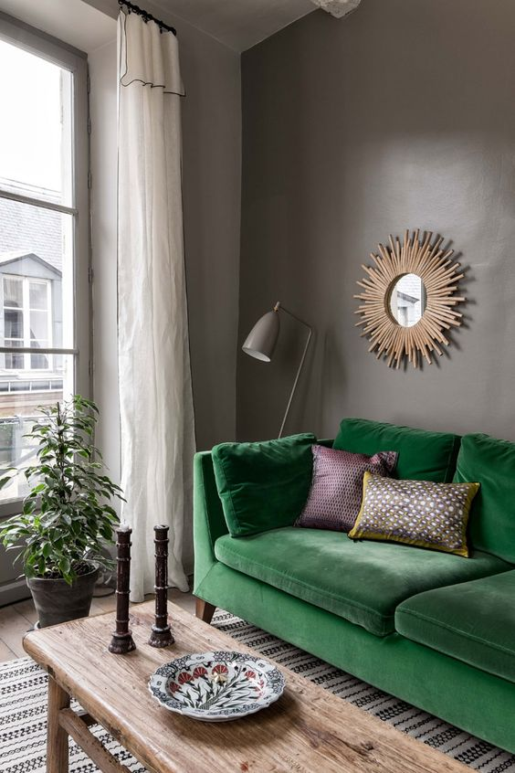 20 a moody living room with grey walls, an emerald Stockholm sofa, a wooden bench, candleholders and a sunbrust mirror looks cool