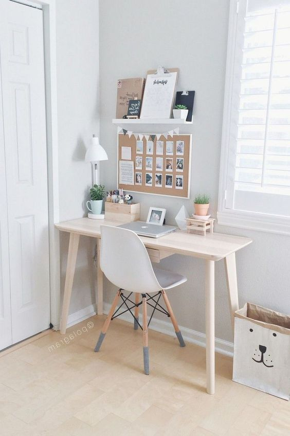 a small Nordic home office with a sleek desk, a white chair, a memo board, a ledge with memos and plants