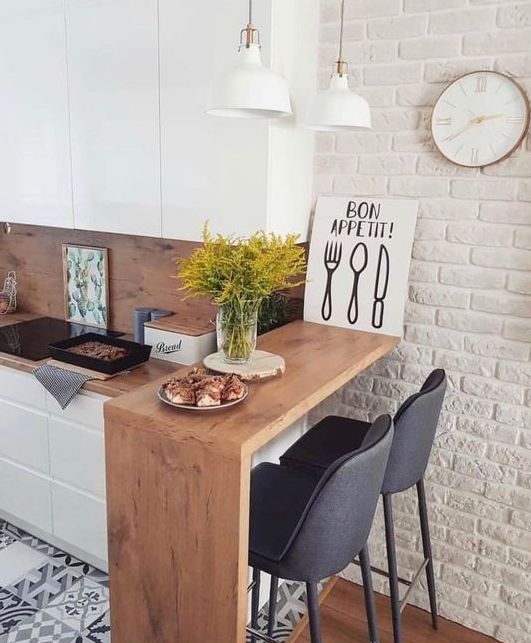 20 a small minimalist kitchen with a raised breakfast bar counter and a couple of comfy chairs plus pendant lamps is cool