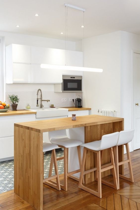 a minimalist white kitchen with butcherblock countertops, a small light-stained kitchen island that matches the countertop