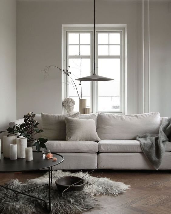 a neutral Scandinavian space with a Stockholm sofa, a round table with candles, a pendant lamp and a faux fur rug is chic