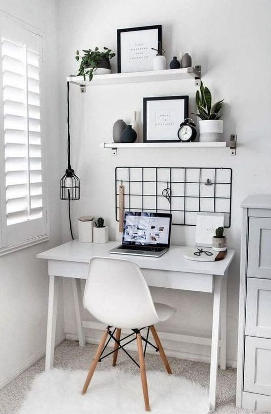 a tiny Scandinavian workspace with a white desk, a grid, shelves with vases and potted plants, a hanging bulb and a white chair