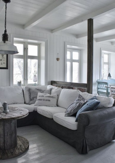 a graphite grey leather Ektorp sofa cover with white cushions, a rough wooden table, retro pendant lamps for a Scandinavian space