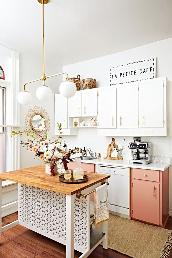a modern coral pink and white kitchen with gold handles, a chic small kitchen island clad with hex tiles that catches an eye