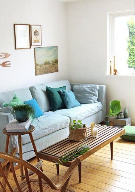22 a relaxed living room with a pastel blue Stockholm sofa, wooden and rattan furniture, blue and grey accessories and a gallery wall