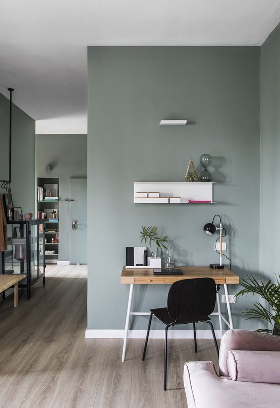a tiny modern plywood desk with a couple of drawers, a box-liek storage unit, a black chair and a table lamp for a Scandi space
