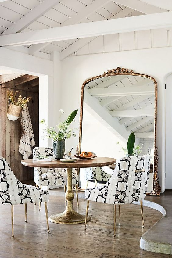 a bold dining space with a round table and printed chairs, an oversized mirror in a gilded frame and potted plants