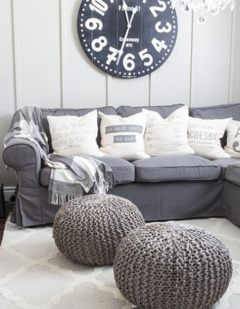 a grey Ektorp sectional sofa and knit poufs, a bold contrasting clock on the wall for a monochromatic farmhouse living room