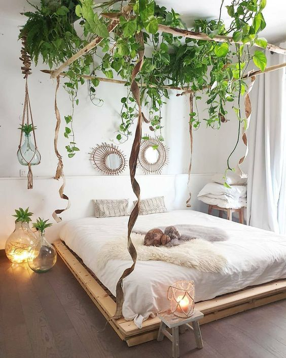 a neutral bedroom with a pallet bed, a hanging burlap frame and hanging green plants is a very creative idea with an airy feel