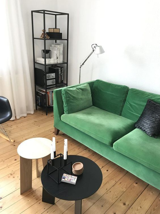 a simple living room in a monochromatic color scheme, with a shelf, round tables and a bold green Stockholm sofa for a colorful touch