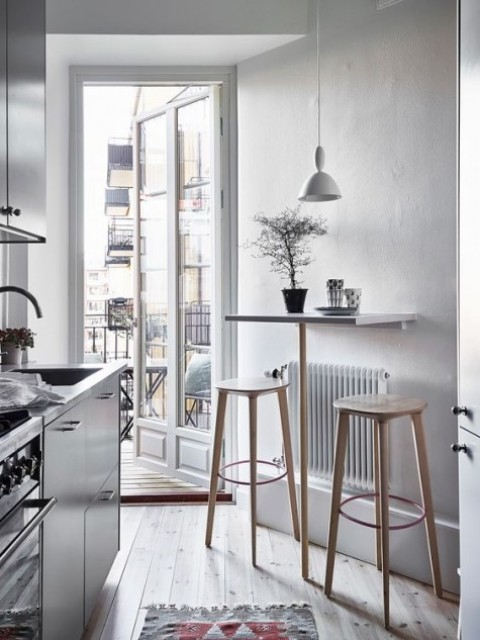 a tiny Scandinavian kitchen with a small tabletop and wooden stools for using them as a breakfast bar