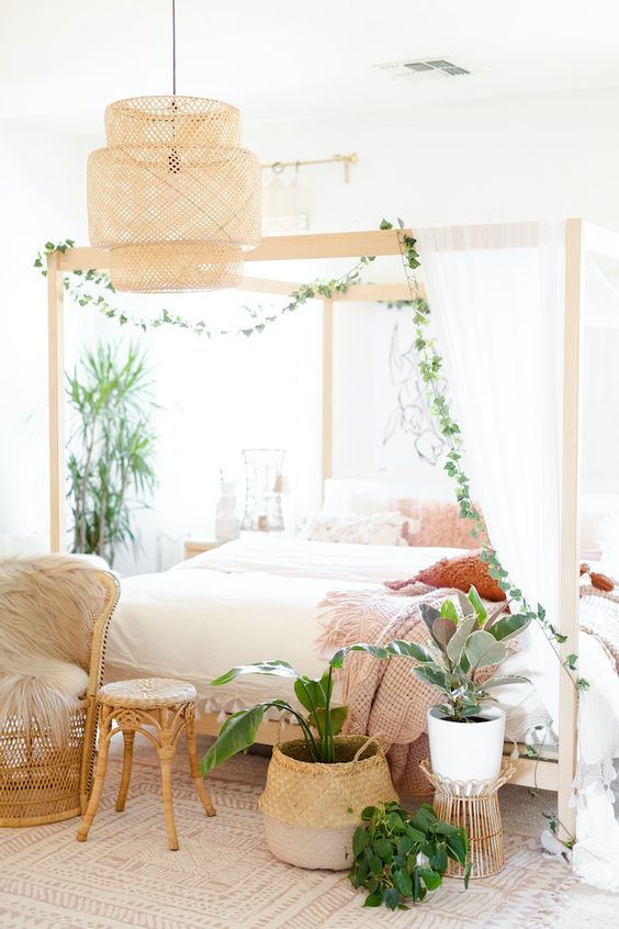 a neutral boho bedroom with a canopy bed styled with neutral curtains and greenery, a pendant wicker lamp, potted plants, rattan chairs