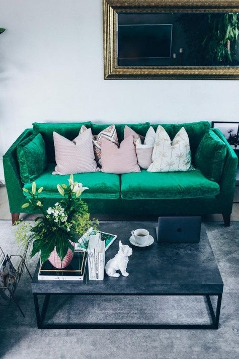 24 a stylish contemporary living room with an emerald Stockholm sofa, a chic table with a stone countertop, a mirror in a gilded frame and fun pillows