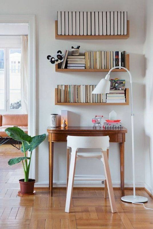 a tiny stained desk, shelves with lots of books, a white stool and a white floor lamp plus a potted plant