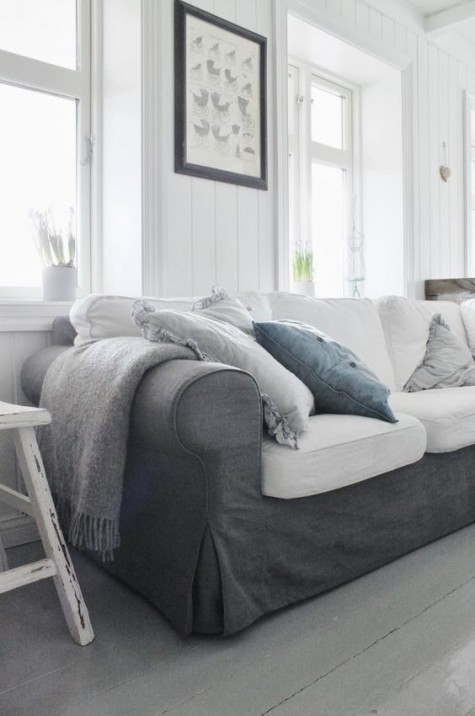 a white Scandinavian space with a grey Ektorp sofa with white cushions, white stools and some potted bulbs is cool