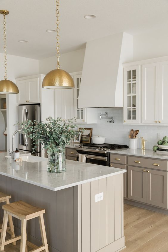 an elegant kitchen with white and greige cabinets, a white tile backsplash, gold pendant lamps on chains