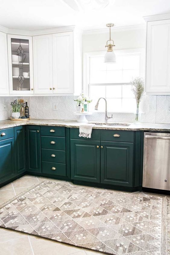 a bold modern kitchen with white and hunter green cabinets, stone countertops, neutral fixtures and appliances