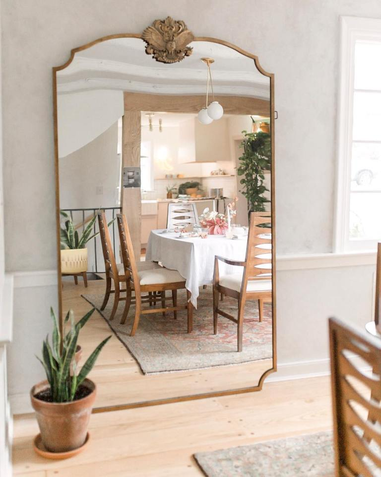 a modern farmhouse dining space with an oversized mirror in a vintage frame that reflects light and makes the space larger