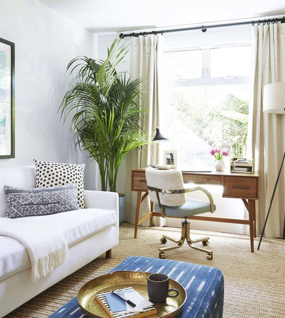 a modern neutral living room with a working space at the window, a creamy sofa, a blue pouf and statement potted plants